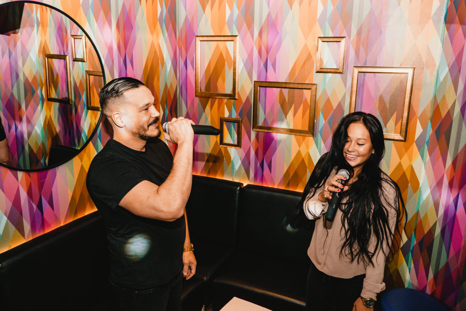 two people singing in a karaoke booth